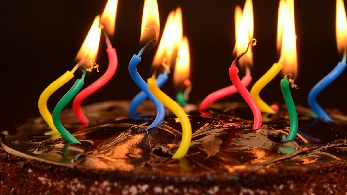 chocolate cake with curly, lit candles